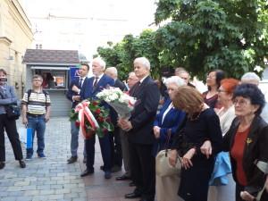 Delegacje z kwiatami przed tablicą